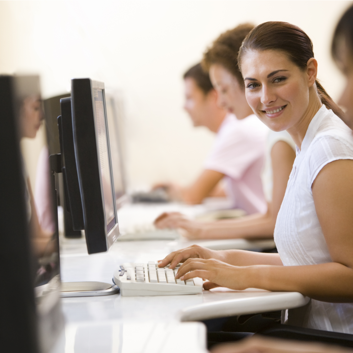 woman smiling typing at computer